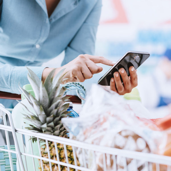 A person using their phone while grocery shopping