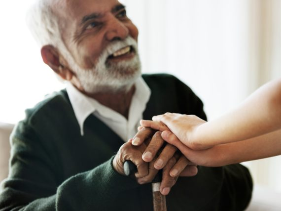 A caregiver placing their hands over the hands of an elderly man