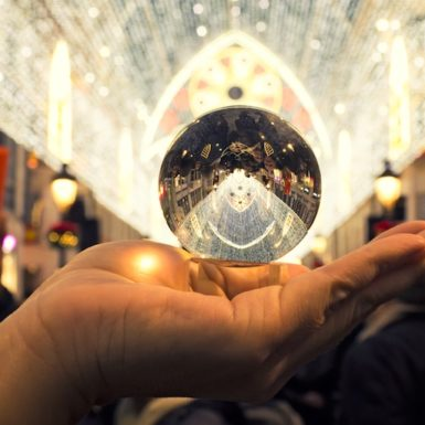 A hand holding a crystal ball to the light