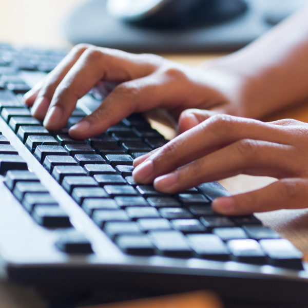 Hands poised over a computer keyboard