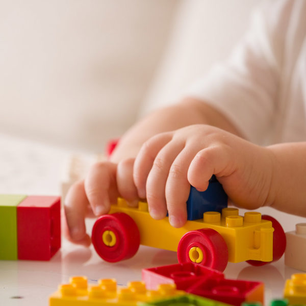 A close up of a child's hands, playing with building blocks